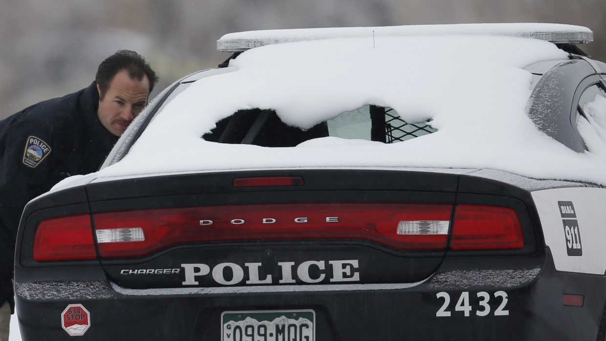 A crime scene investigator looks over a police vehicle damaged during Friday's shooting spree near a Planned Parenthood clinic Sunday, in northwest Colorado Springs.