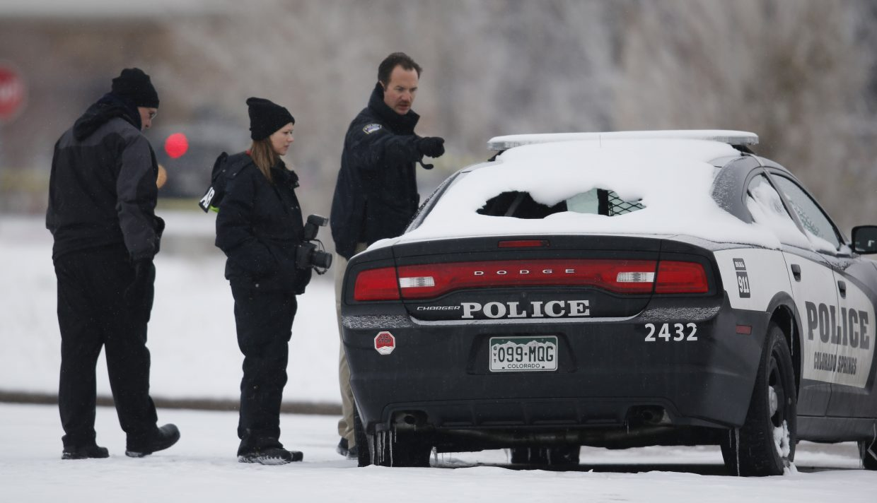 Crime scene investigators look over a vehicle damaged during Friday's shooting spree near a Planned Parenthood clinic Sunday, in northwest Colorado Springs.