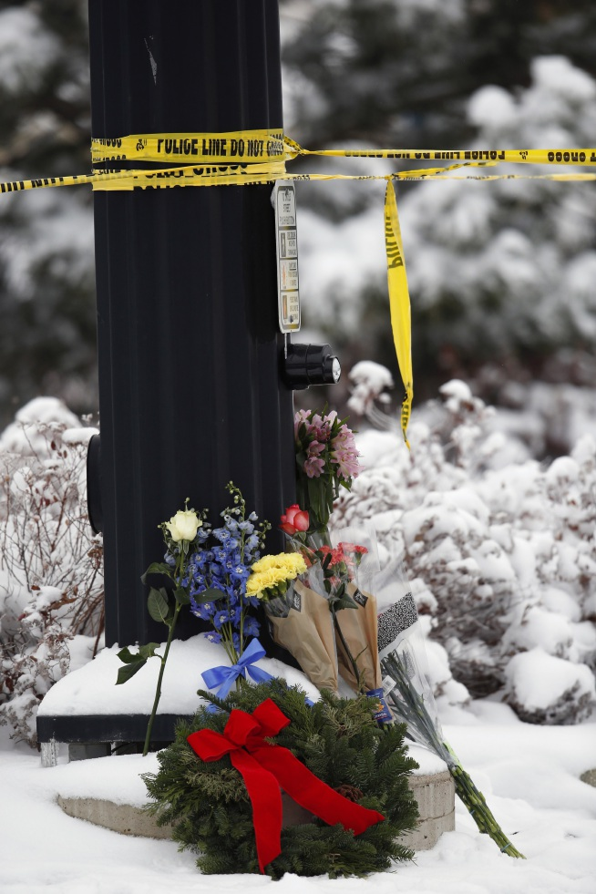 Flowers rest under police tape near a Planned Parenthood clinic Saturday, Nov. 28, 2015, in Colorado Springs, Colo., after a deadly shooting Friday. A gunman engaged in an hours-long standoff before surrendering at the clinic.  (AP Photo/David Zalubowski)