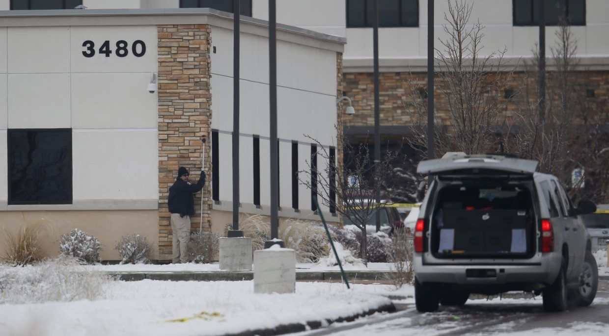 A police investigator holds up a measure along the wall of a Planned Parenthood clinic building, while gathering evidence from the Friday shooting outside the clinic Sunday, in northwest Colorado Springs.
