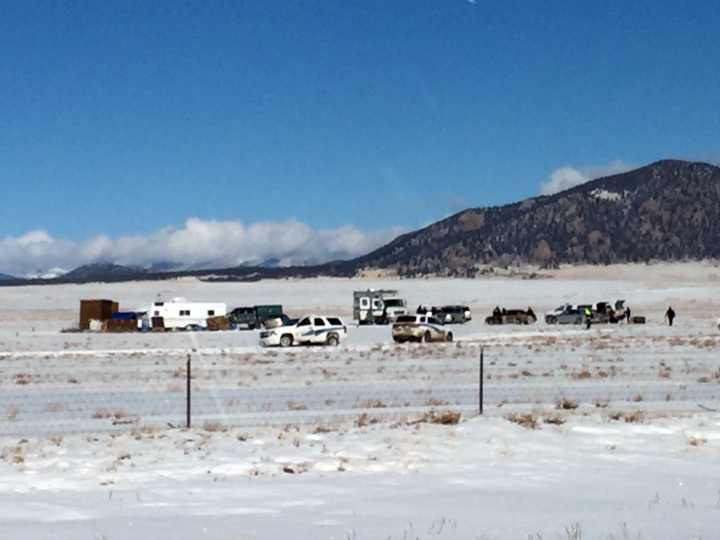 Investigators search an area where Robert Lewis Dear lived, far left, near the town of Hartsel, Colo., Saturday. Dear is a suspect in Friday's deadly shooting at a Planned Parenthood clinic in Colorado Springs.