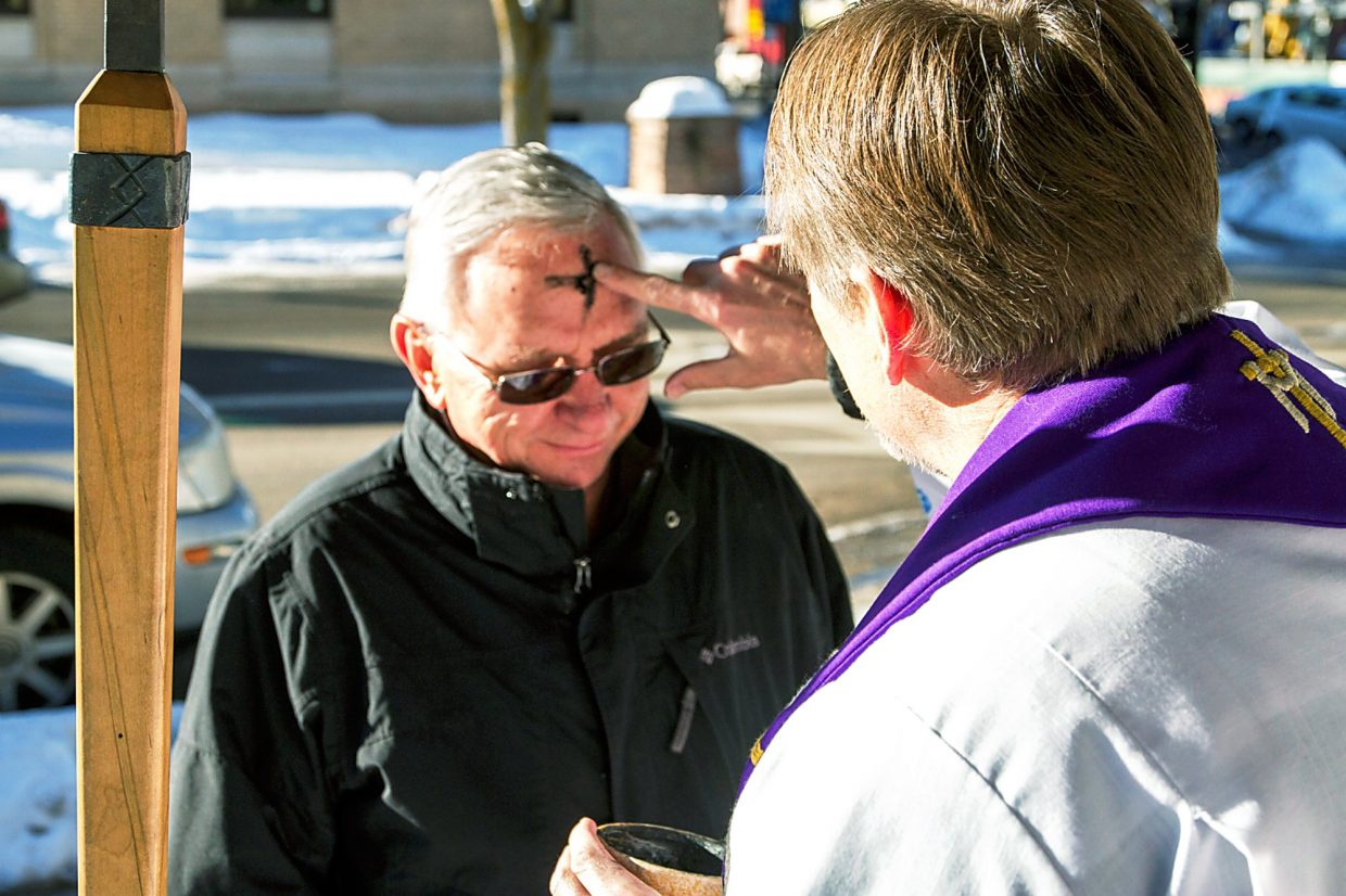Ricky Smith received a cross on his forehead for Ash Wednesday in Centennial Park Wednesday morning. Paster Jeff Carlson of Good Shepherd Lutheran Church in Glenwood Springs spent the morning despensing ashes to those interested. The ashes used to mark a cross on a person's forehead symbolize the belief that God created man from ashes and that man returns to ashes after death. Ash Wednesday is the beginning of Lent, 40 days that lead to Easter.