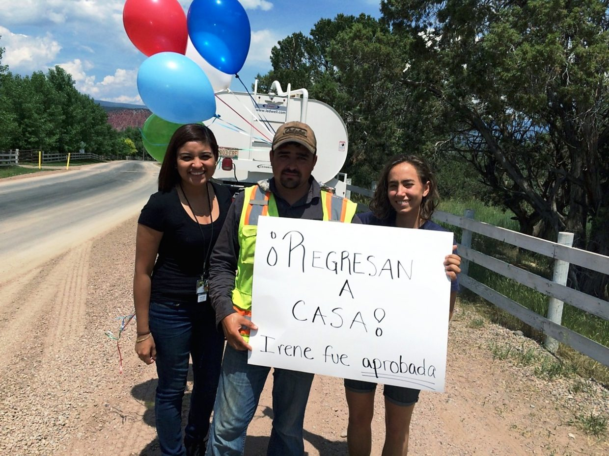 """Anahi Araiza, left, and Sophia Clark, right, broke the news to Alberto Chavez-Tena that his wife's waiver, a key step in her gaining U.S. residency and bringing the couple's U.S. citizen sons home, apparently has been approved. The sign reads """"They're coming home. Irene was approved."""""""