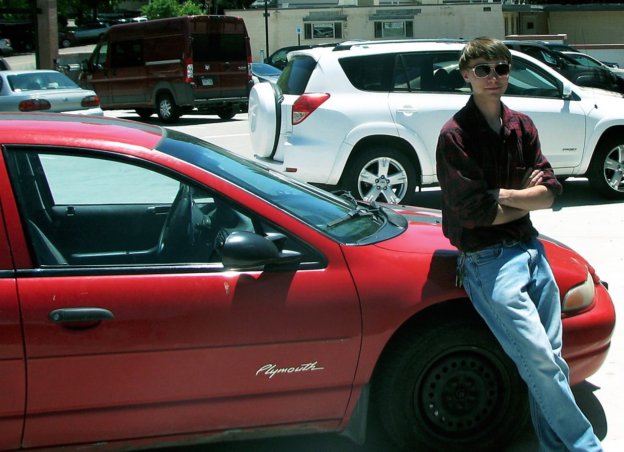 Anson Lemmer stands by his 1998 Plymouth Breeze, which he used last summer in his pizza delivery job for Uncle Pizza in Glenwood Springs.