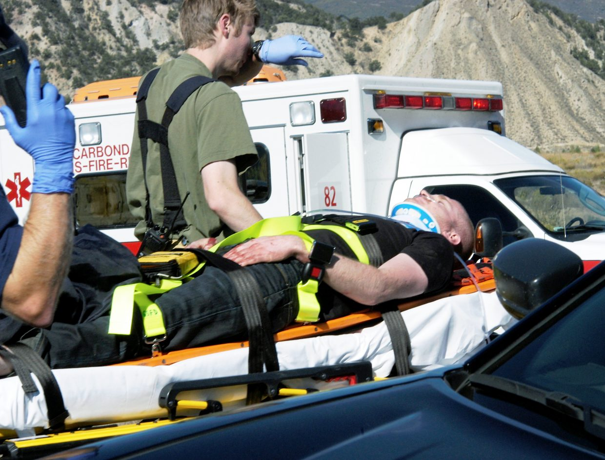 Emergency workers transport one of the victims from a June plane crash south of Glenwood Springs to a waiting ambulance.