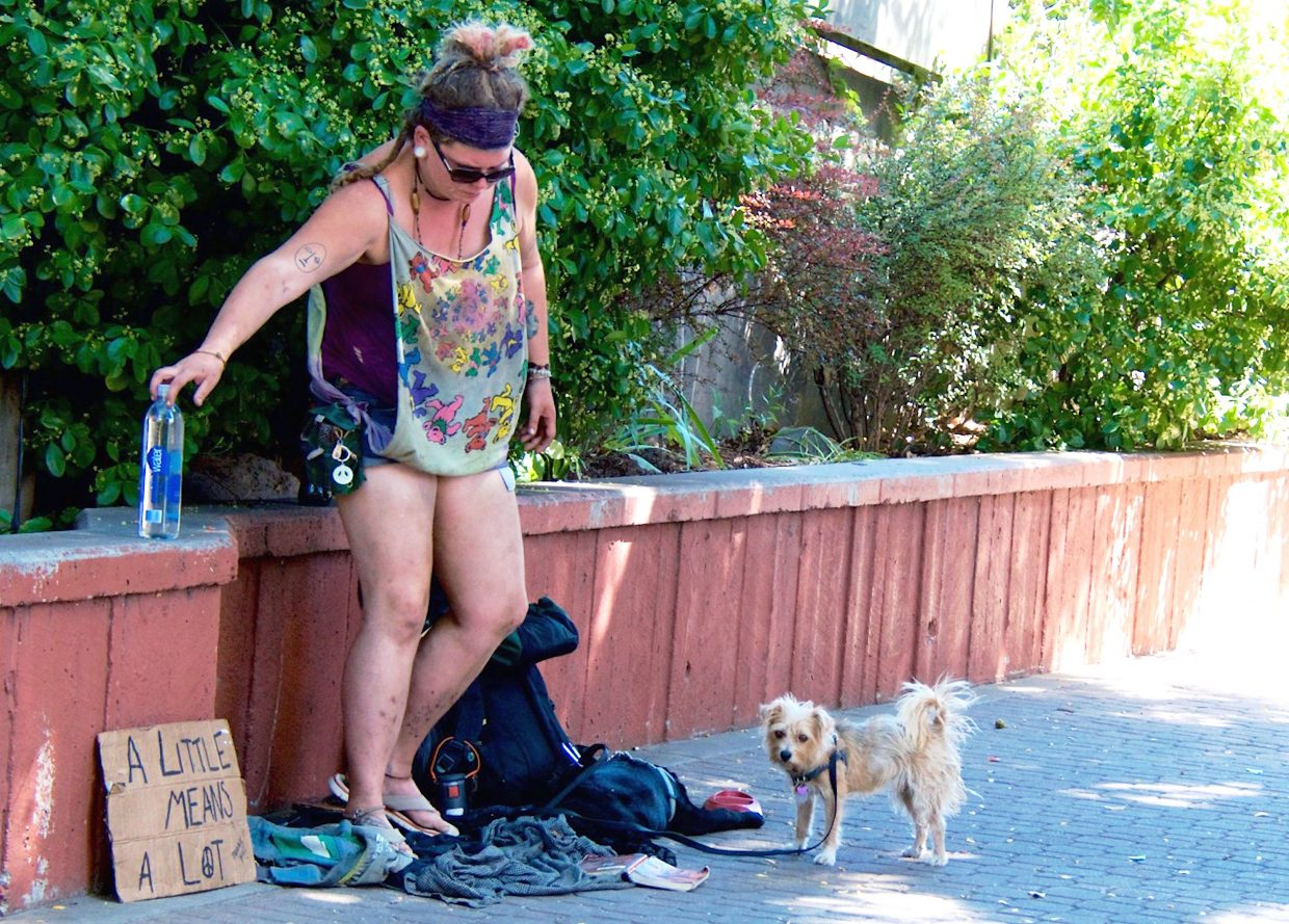 K. Archer, gives her dogs water along the pedestrian plaza on the west side of the Grand Avenue Bridge in Glenwood Springs in August. She was a regular fixture part of the summer panhandling on the public plaza.