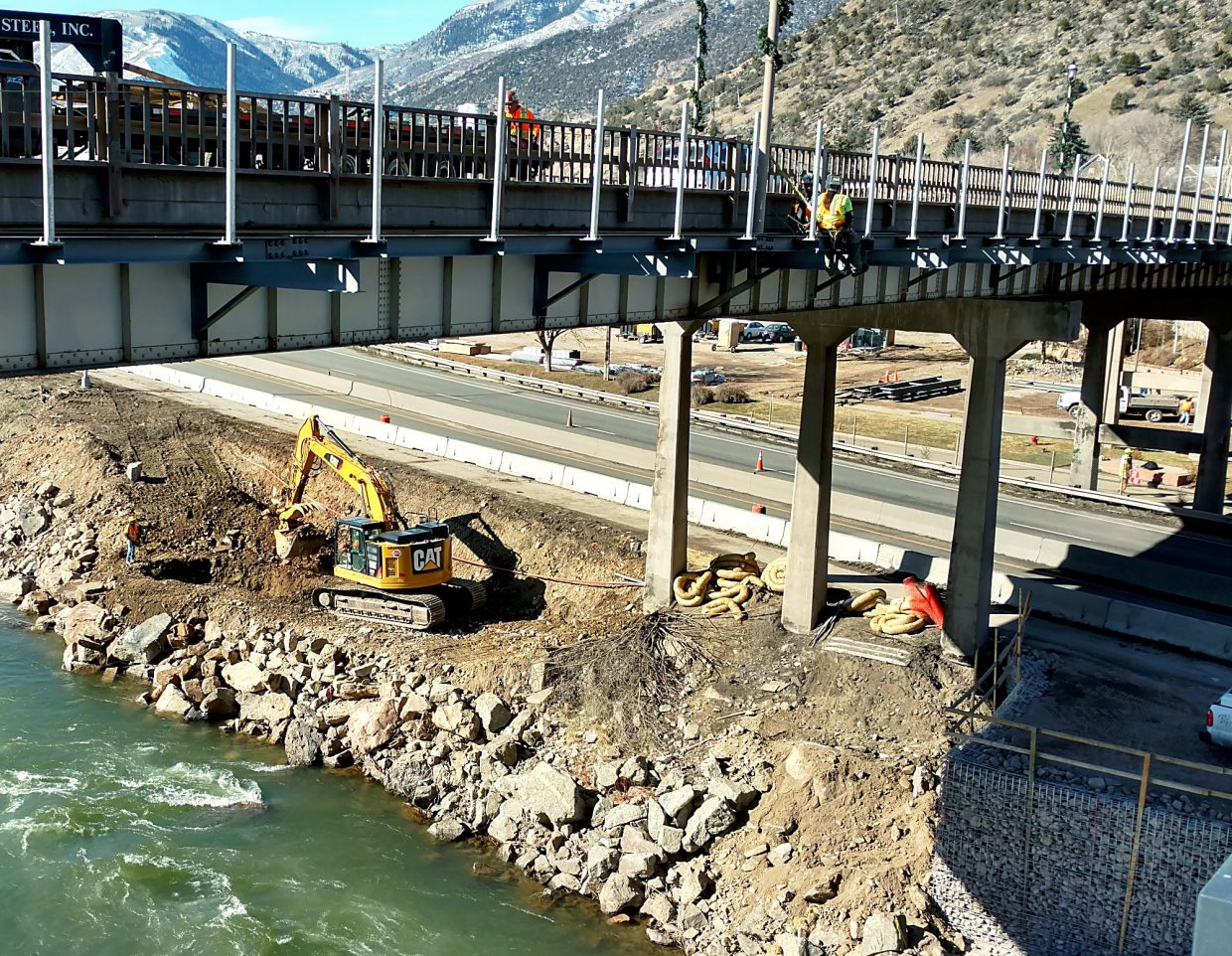 Work continued Friday in the early stages of the Grand Avenue bridge project, with bracket beams being set alongside the traffic bridge for a temporary pedestrian bridge and equipment prepping the Colorado River's banks for future work.
