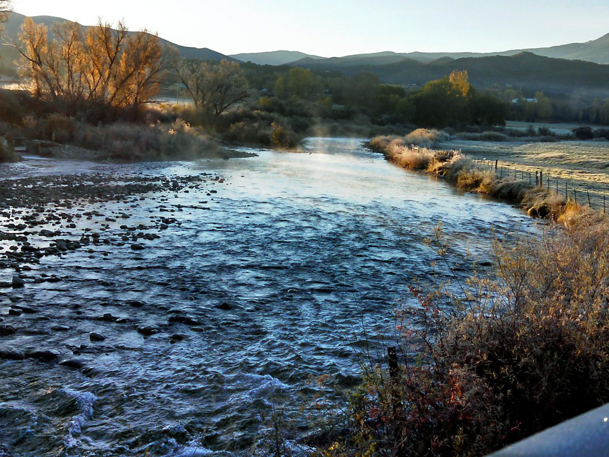 Steam rises from the Crystal River Saturday as the sun rises over hills to the east.