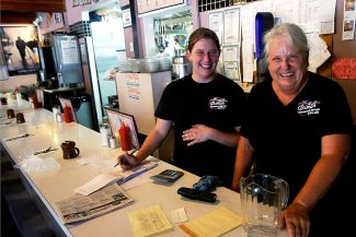 Jennifer Burkdoll, left, and Pam Lloyd, who are waitresses at the 19th Street Diner in Glenwood, laugh and smile as they talk about the giving spirt of  customers Thursday who paid for each others' meals for over three and a half hours.