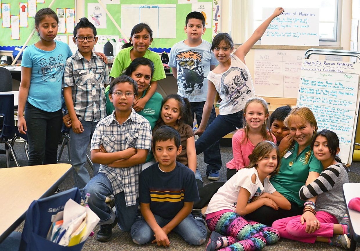 Eloisa Duarte (bottom right) and Laura Topete (left of center) with third-graders at Crystal River Elementary School. Topete is a parent mentor for the Valley Settlement Project.