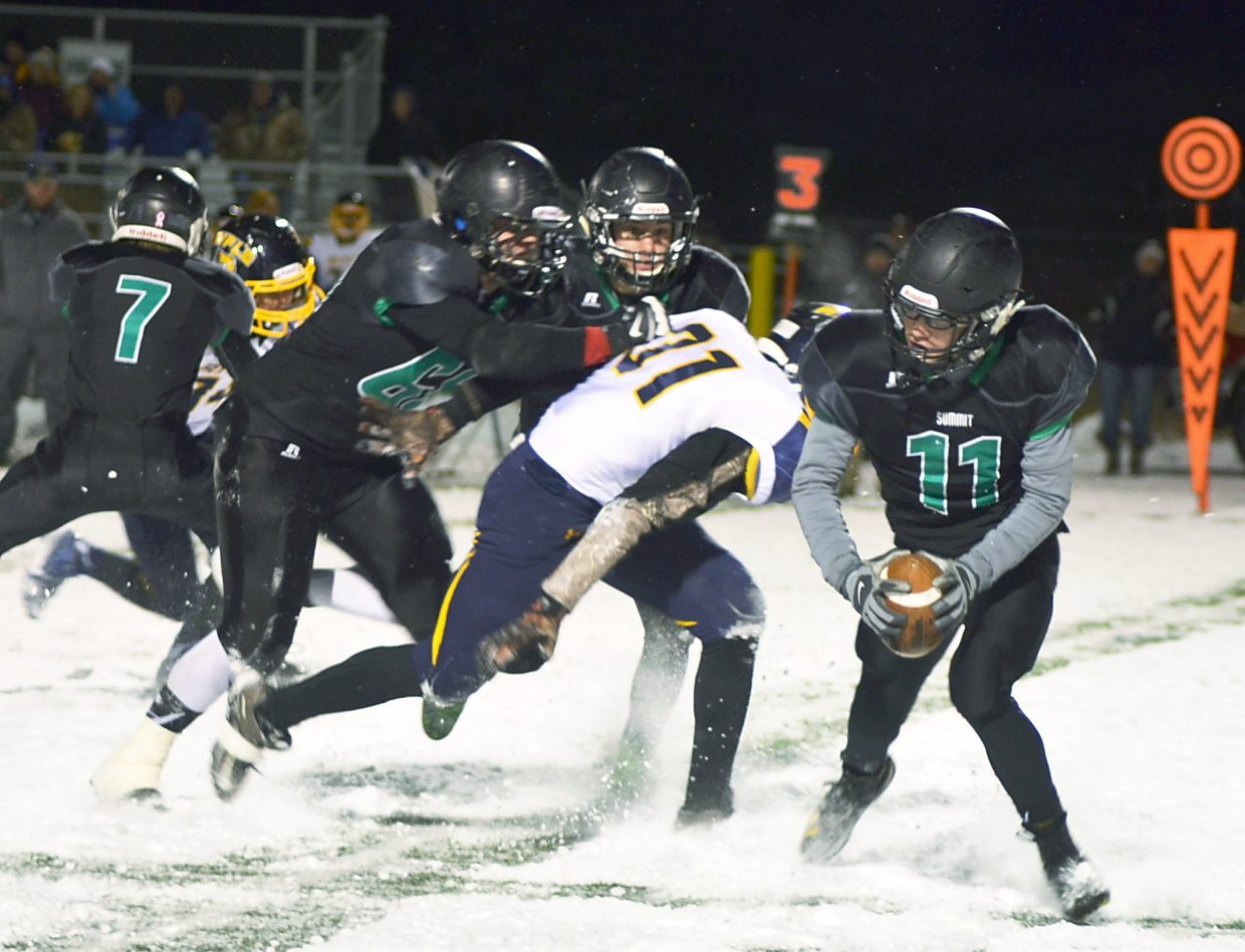 Rifle defenders close on Summit Tigers senior quarterback Riley Beck in the last regular season game this year, shot by @sumcosports