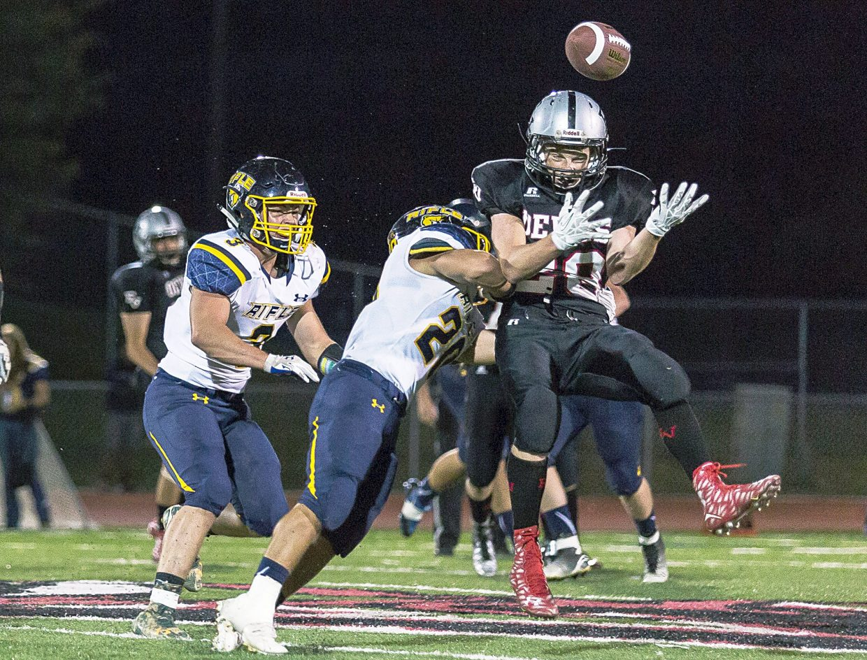Eagle Valley's Kyle Williams loses possession of the ball during an incomplete pass after taking an impact from Rifle's Ty Leba.