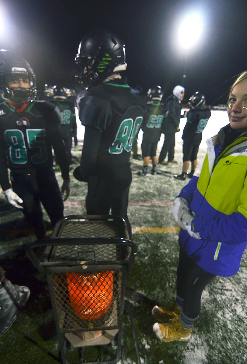 Players and assistants huddle around a heat lamp before kickoff against Rifle at the Summit home closer on Nov. 6. The Tigers lost, 6-55.