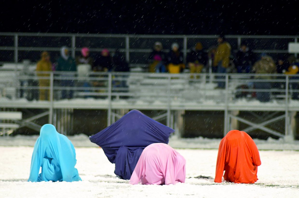 A group of students with the Summit Dancers After School Poms Squad performs a costumed Halloween routine at halftime of the Summit home football game on Nov. 6. The group of elementary-aged dancers braved the cold and snow for a routine set to