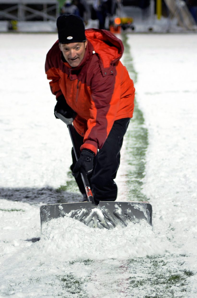A volunteer shovels the yard lines at halftime of the Summit football home closer against Rifle on Nov. 6. The Tigers lost, 6-55.