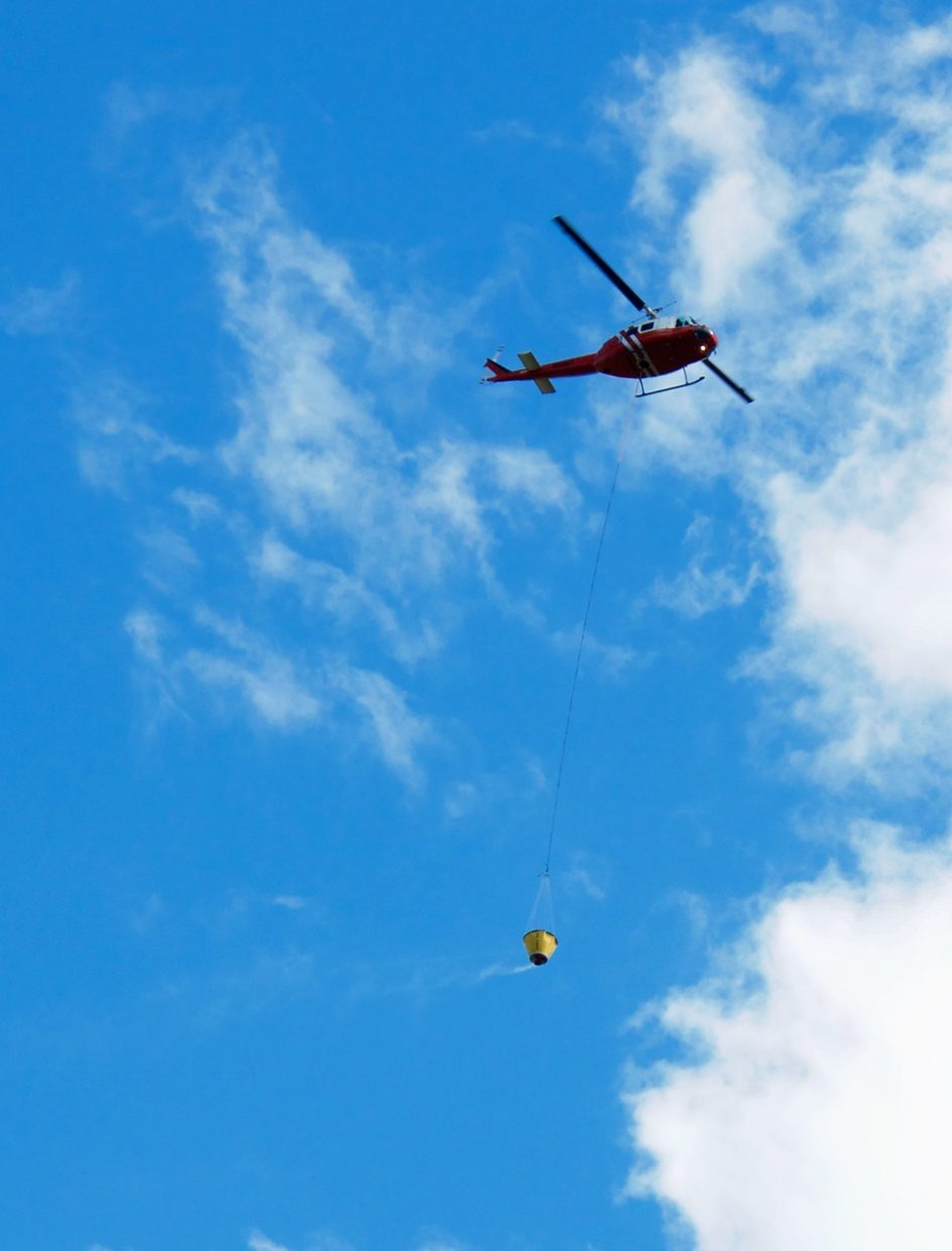 A helicopter flies with a bucket Friday afternoon to help douse a wildfire blaze near Red Canyon Road south of Glenwood Springs.