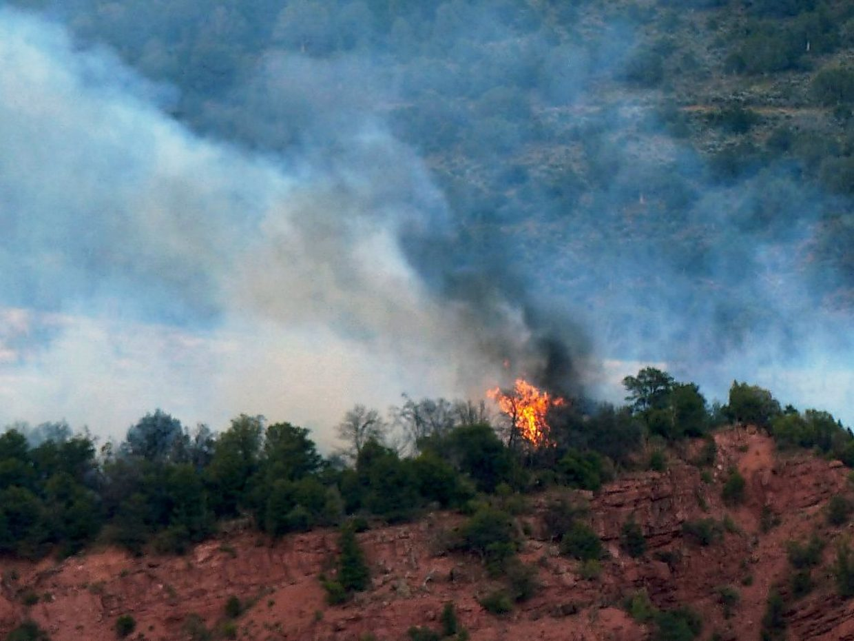 Flames lick toward a ridge south of Glenwood Springs on Friday.