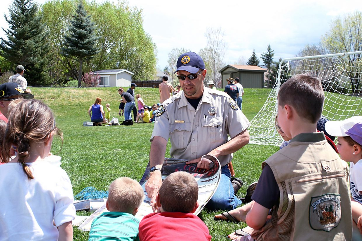 Brian Gray, district game warden with Colorado Parks and Wildlife, explains how to identify the various types of fish to a group of eager children Saturday. The annual fishing derby seems to draw more and more kids, Gray said afterward.
