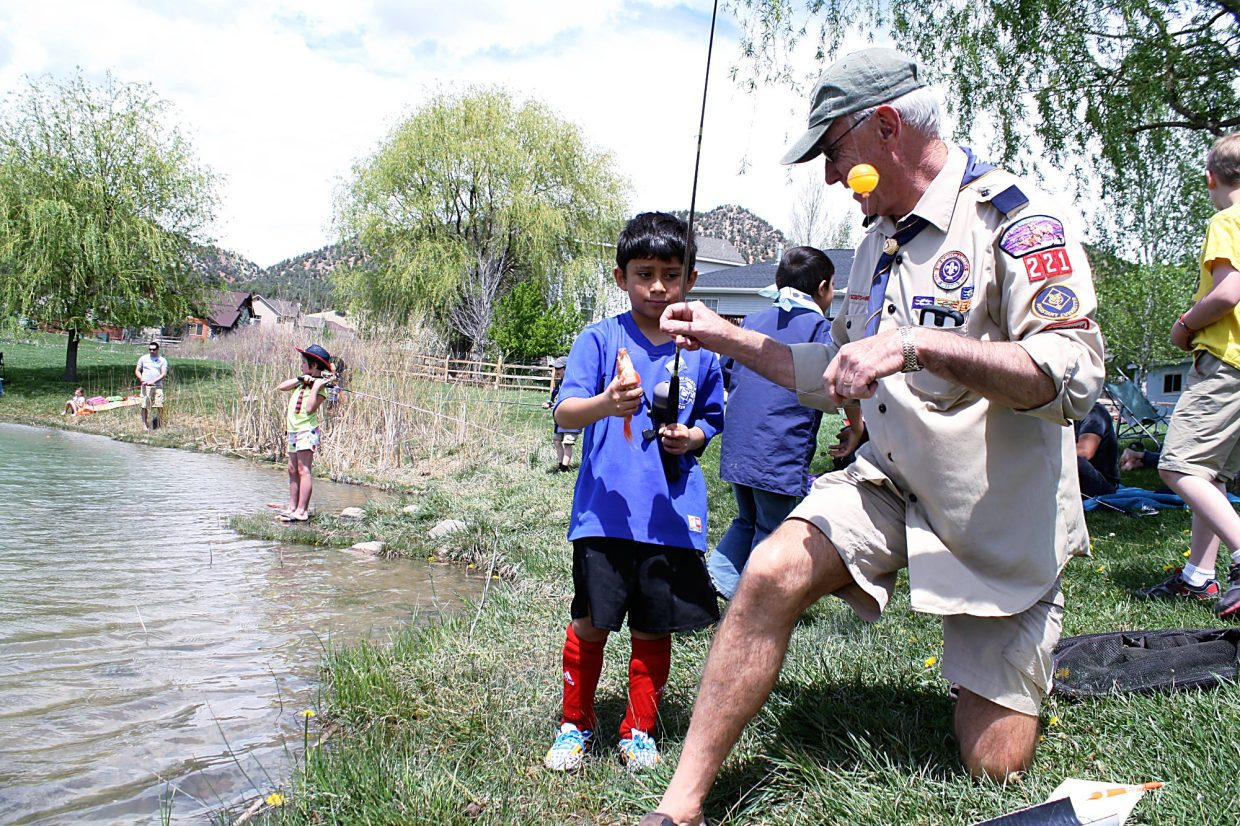 John Harcourt with New Castle Cub Scouts Pack 221 helps scout Josiah Diaz pull a fish out of the pond at Alder Park Saturday. Approximately 100 children roamed around the park for the annual Mr. T's Fishing Derby. Diaz caught the second fish of the day.