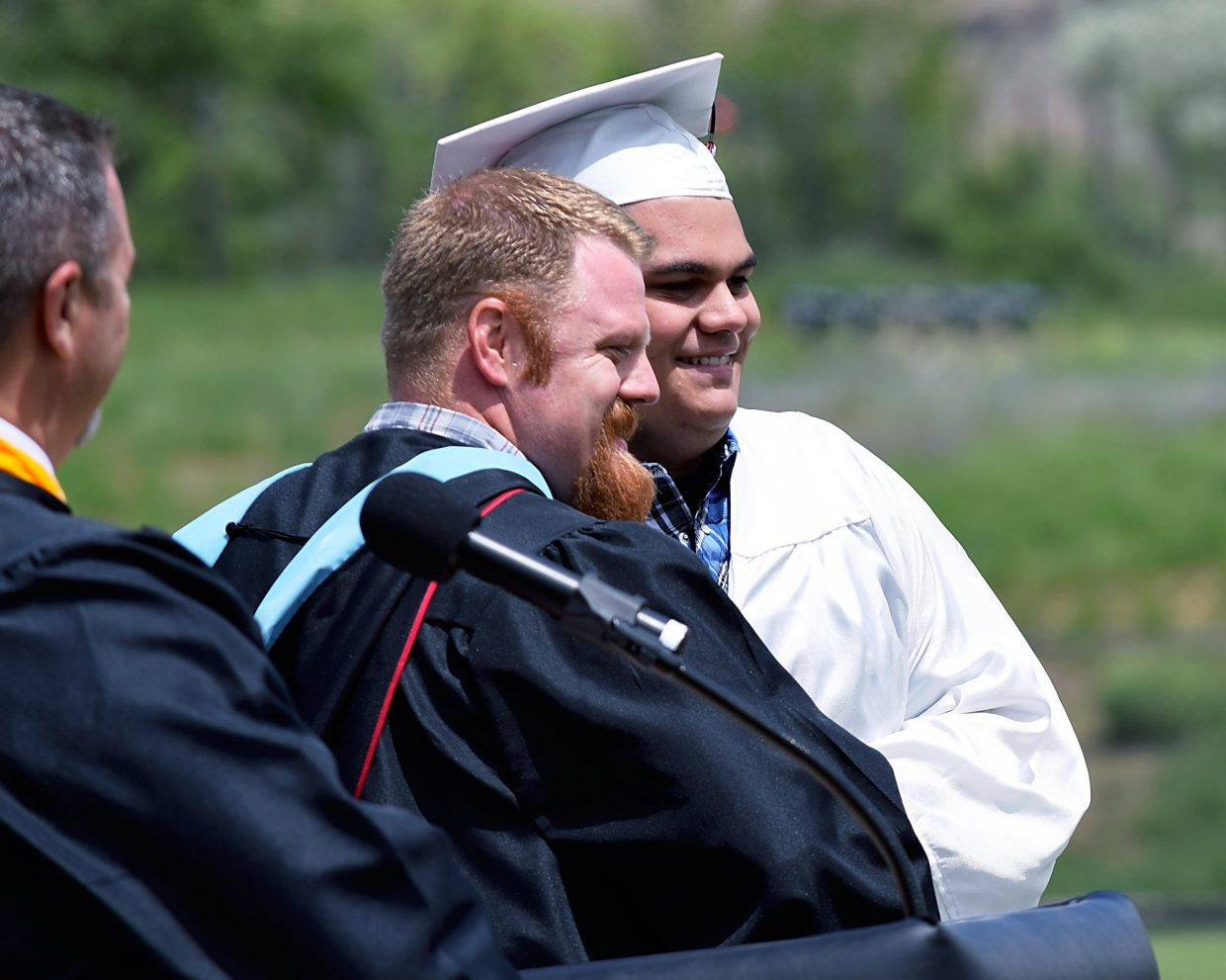 Grand Valley High Principal Ryan Frink, left, congratulates Layn Ryden after Ryden received his high school diploma during the school's graduation ceremony in Parachute on Saturday morning.