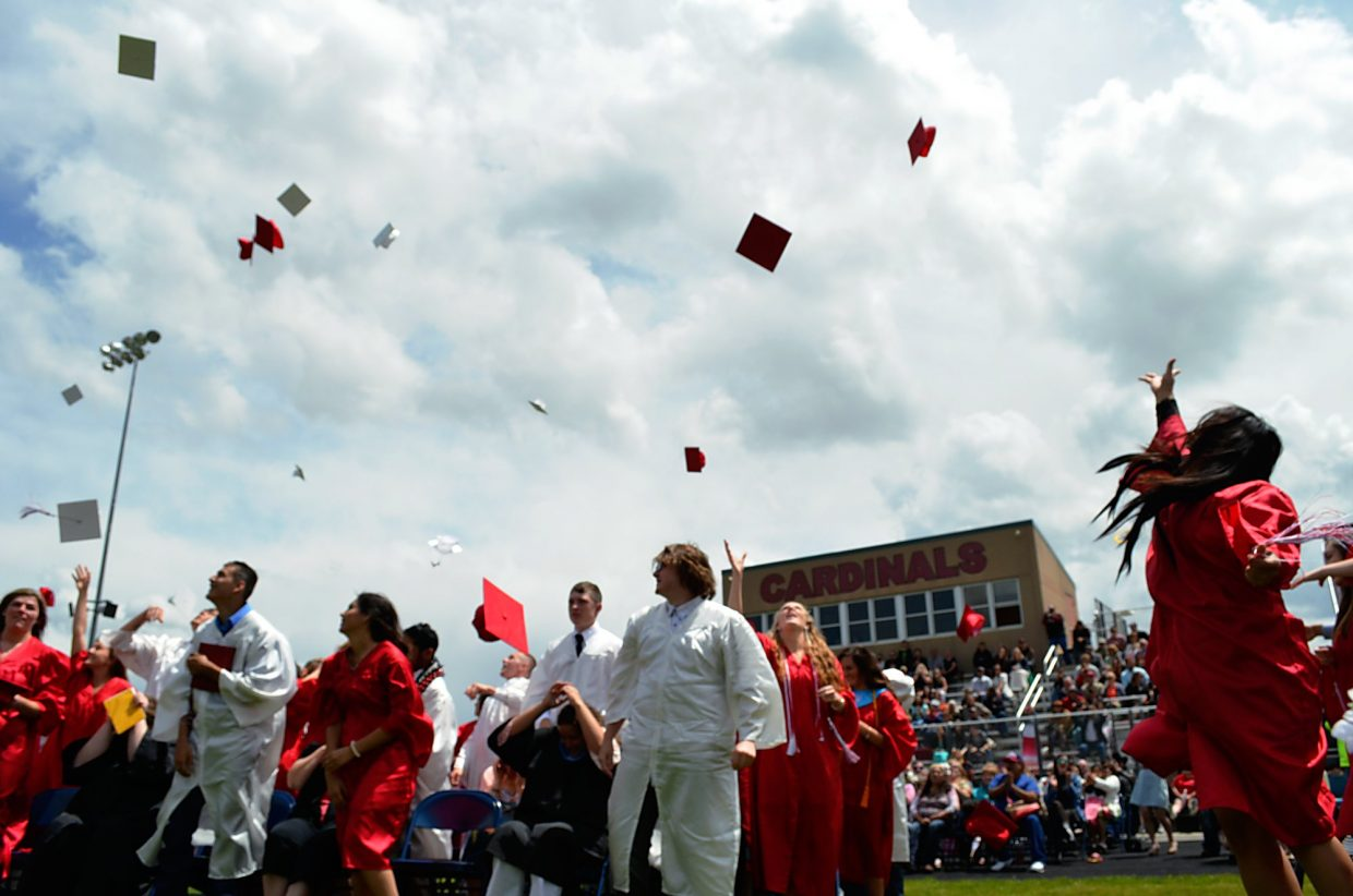 Grand Valley High School graduates toss their mortar boards in the air following the school's graduation ceremony on Saturday morning in Parachute.