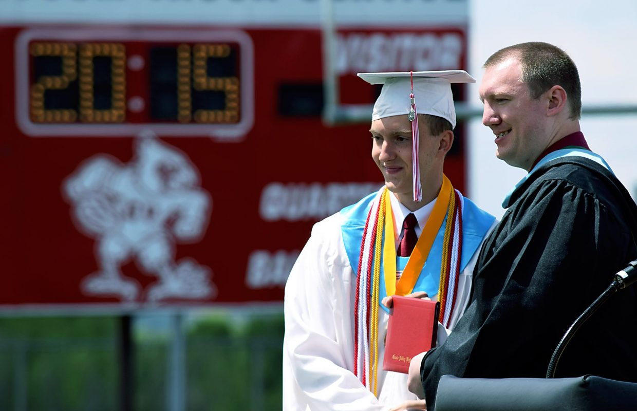 Grand Valley High School valedictorian Ben Coleman receives his high school diploma from teacher Travis Porter during the school's graduation ceremony Saturday morning in Parachute.