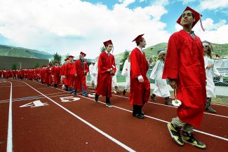 Christopher Mullen Post Independent Graduating seniors parade across the track on their way to their seats, at Stubler Memorial Field during the Glenwood Springs High School Graduation May 31.