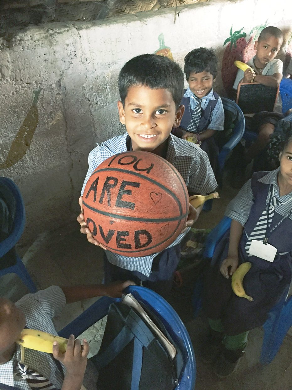 A Dalit boy holds a basketball bearing the words