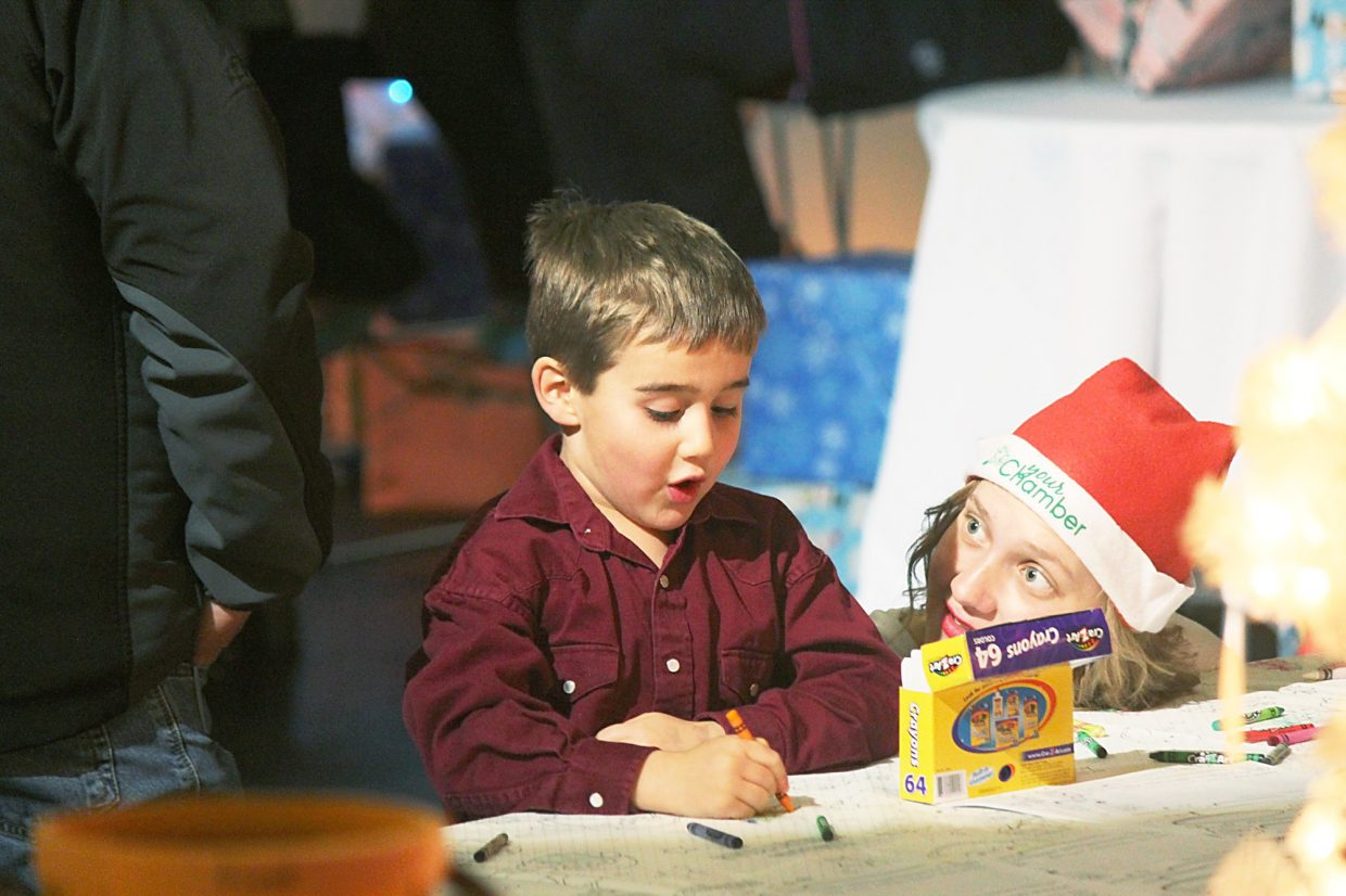 Gretchen Jurmu, right, helps Beau Maddalone with his list for Santa.