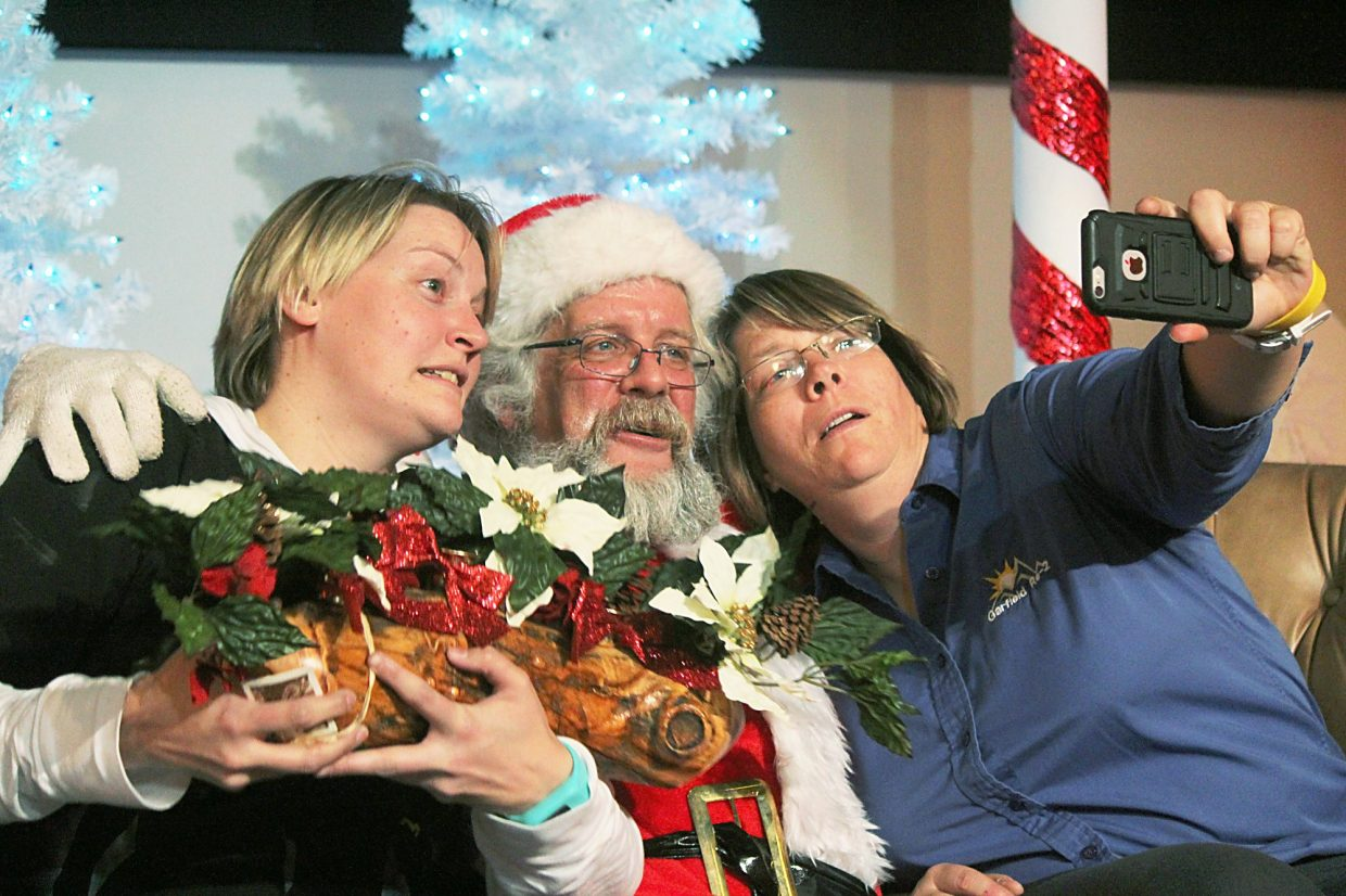 The winner of the yule log scavenger hunt, Amanda Bingman, left, and Theresa Hamilton take a selfie with Santa Friday at the New Ute Events Center.