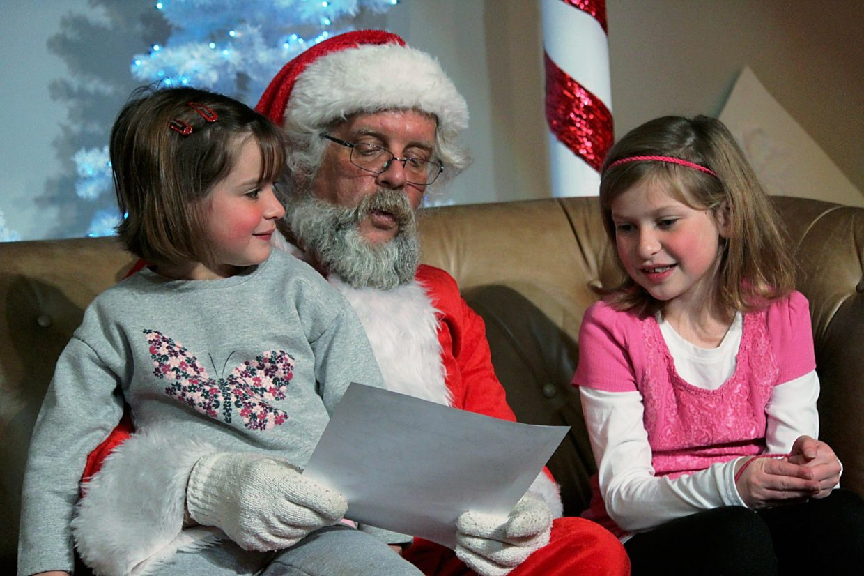 Maci, left, and Elizabeth May share their Christmas wish list with Santa Friday at the New Ute Events Center.