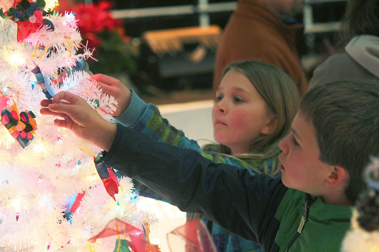 Jacob Cox, front, and Reagan Thompson take a closer look Friday at ornaments on a tree in the New Ute Events Center.