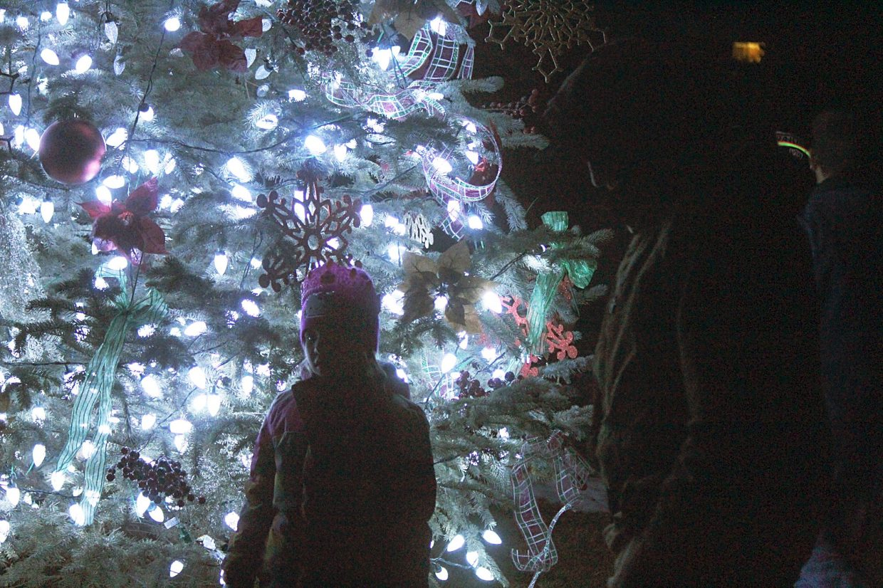 Keira Portlock takes a closer look at the Christmas tree in Centennial Park Saturday shortly after a tree lighting.