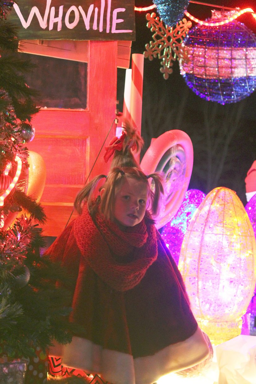 Dressed as Cindy Lou, Brook Daniels sits on a Grinch-themed Elder Construction, Inc.