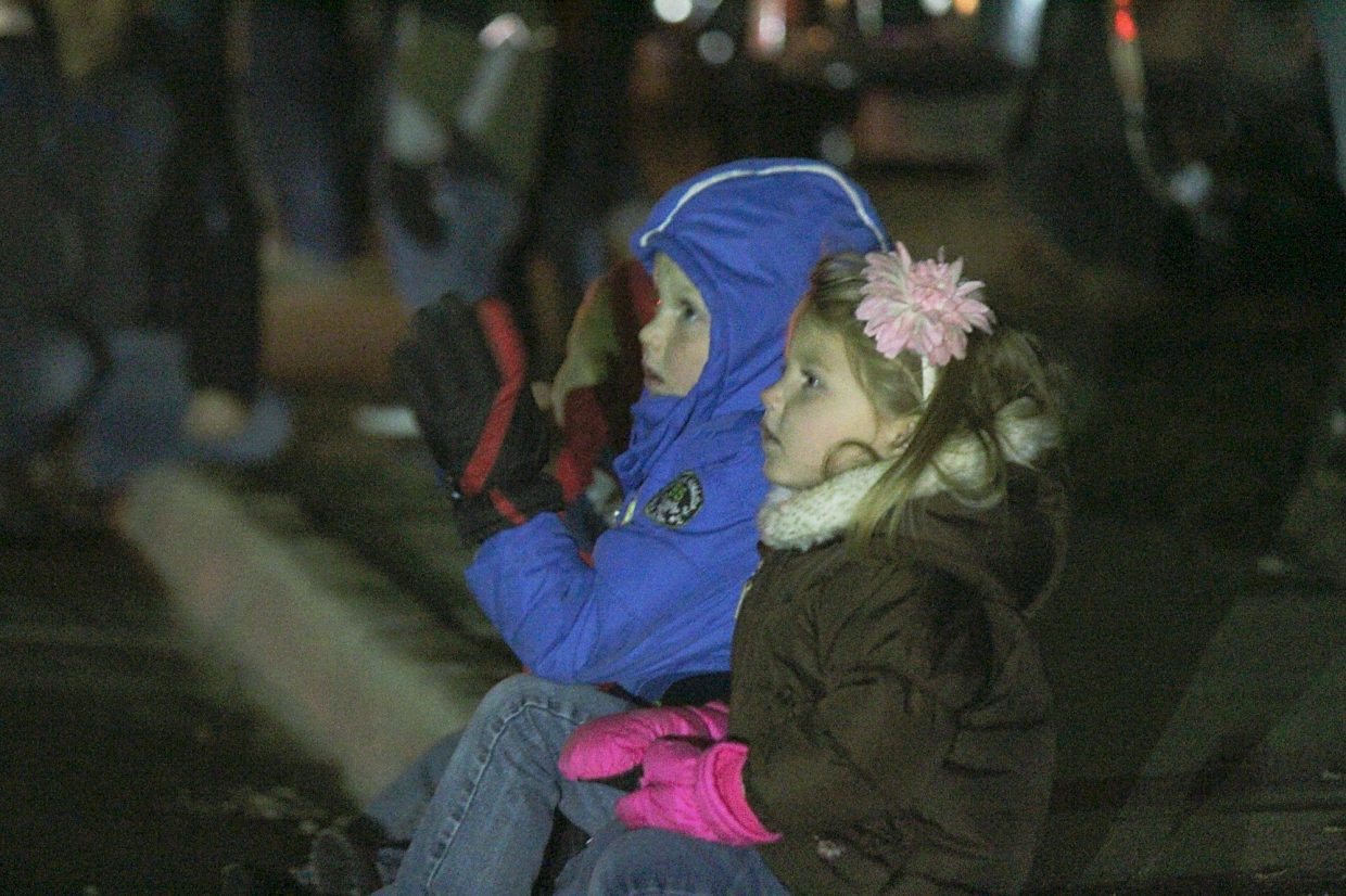 The Duttons watch the 2015 Hometown Holiday Celebration Parade of Lights on Railroad Avenue. From front to back are Brayley, Brantley and Brawley.