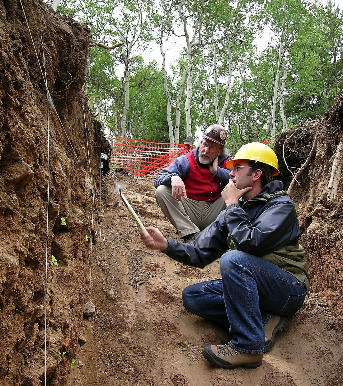 Geologists Matt Morgan and Robert Kirkham of the Colorado Geological Survey look for evidence of movement along a fault after trenching through soils deformed by a fault and mapping their internal structure.
