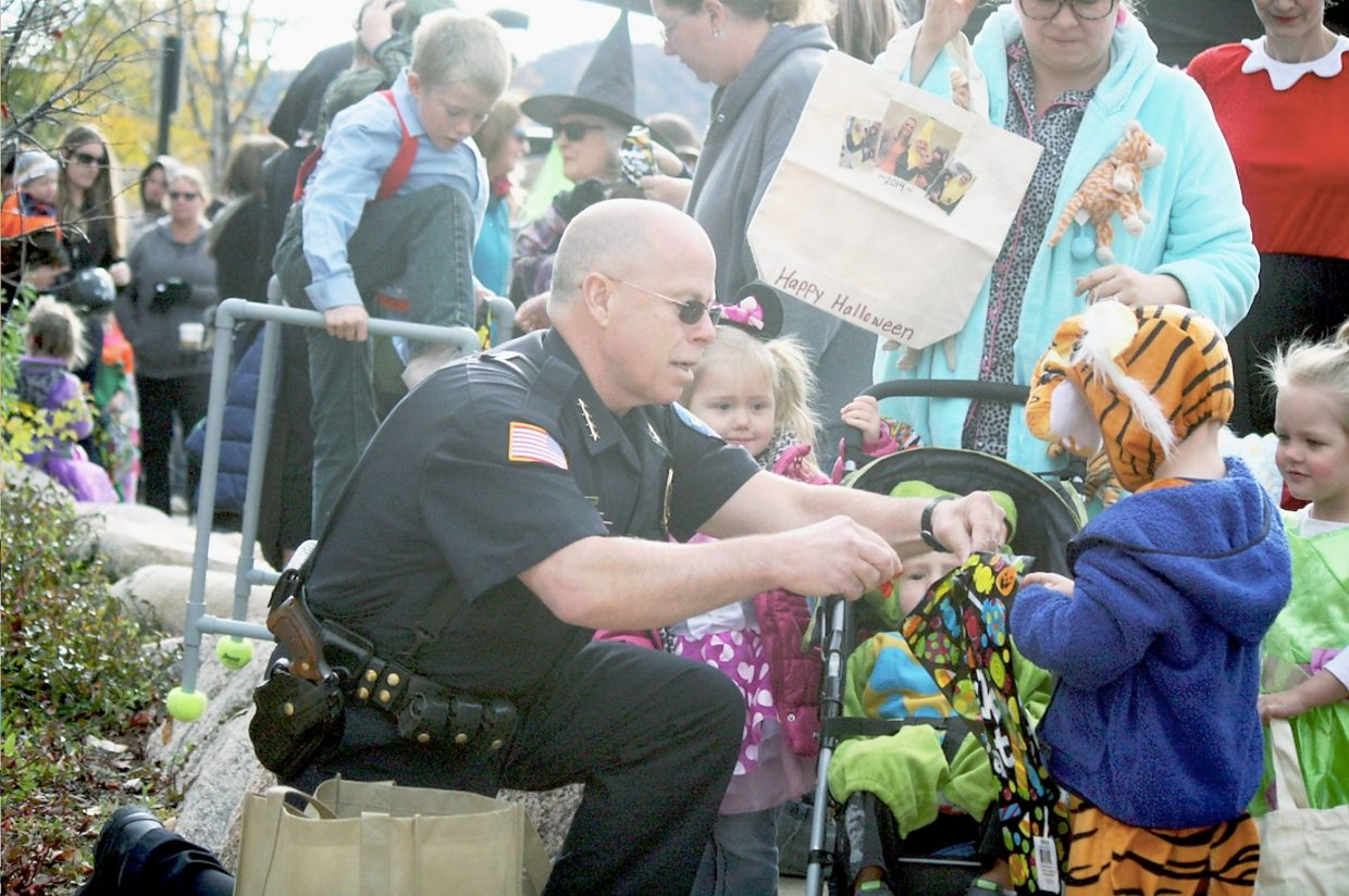 Rifle Police Chief John Dyer hands out candy Friday, Oct. 30.