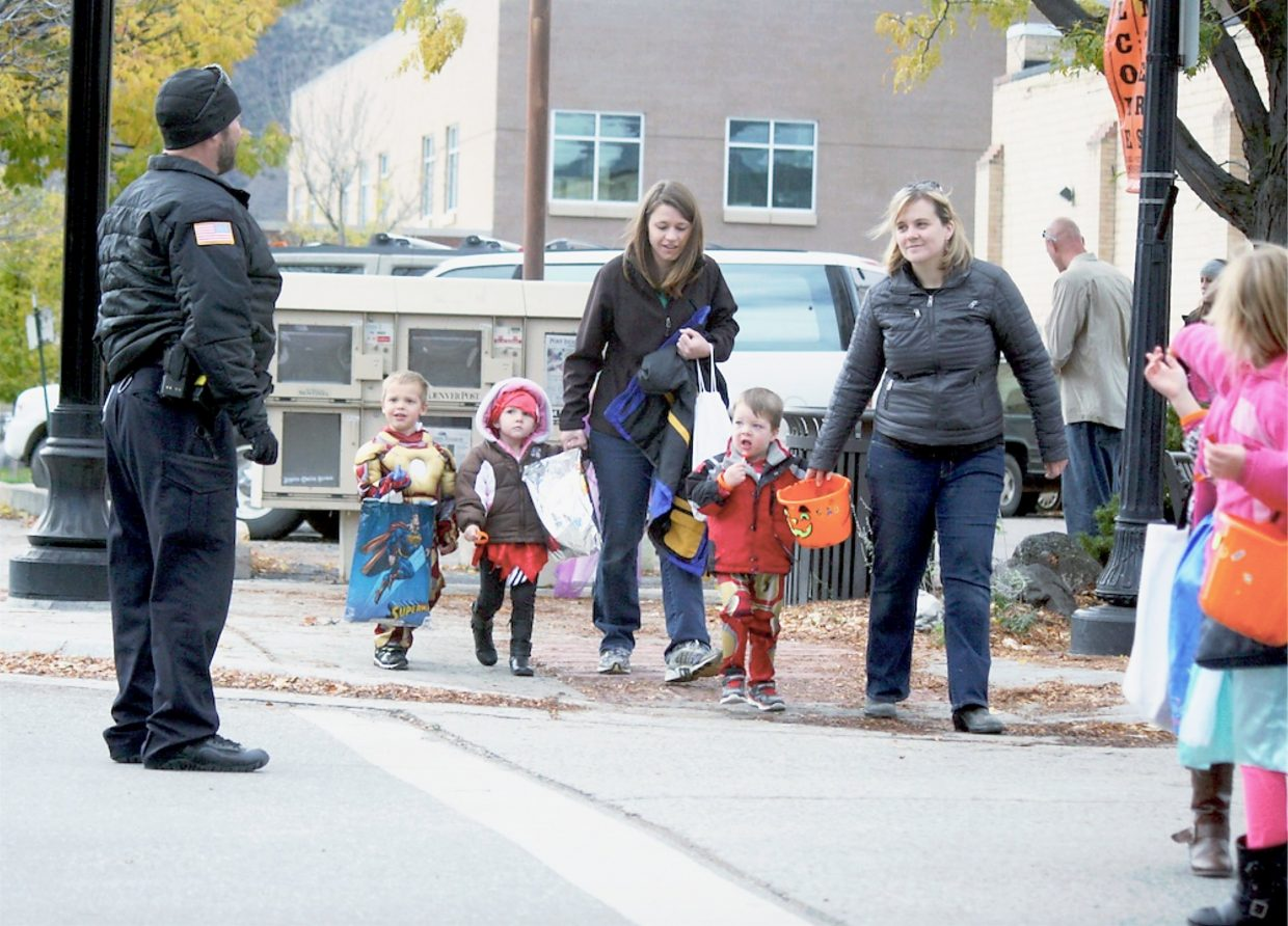 A group of trick-or-treaters cross the street at the intersection of East Avenue and Third Street during the annual Rifle Branch Library Halloween Parade Friday, Oct. 30.