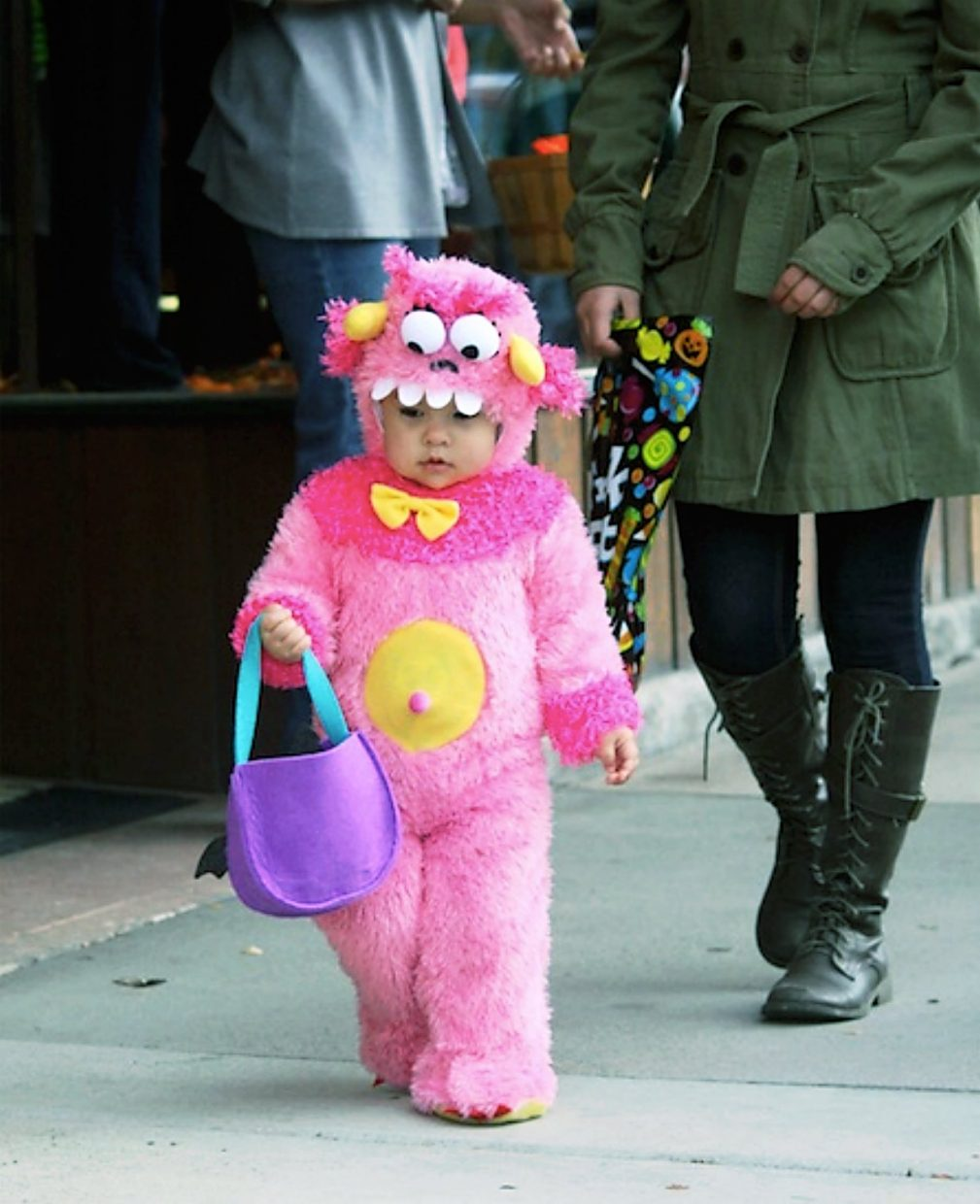 Stephanie Wittrock, 1, walks toward some business owners passing out candy on Third Street in Rifle.