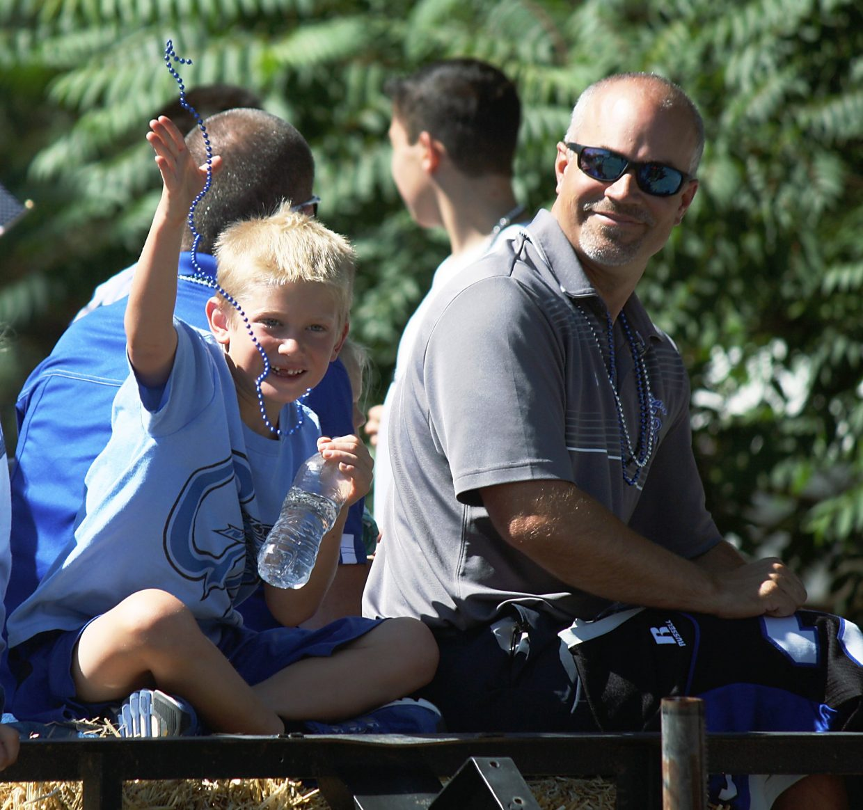 A young boy on the Coal Ridge High School booster club float tosses a set of blue beads near the intersection of Ninth Street and Orchard Avenue Saturday.