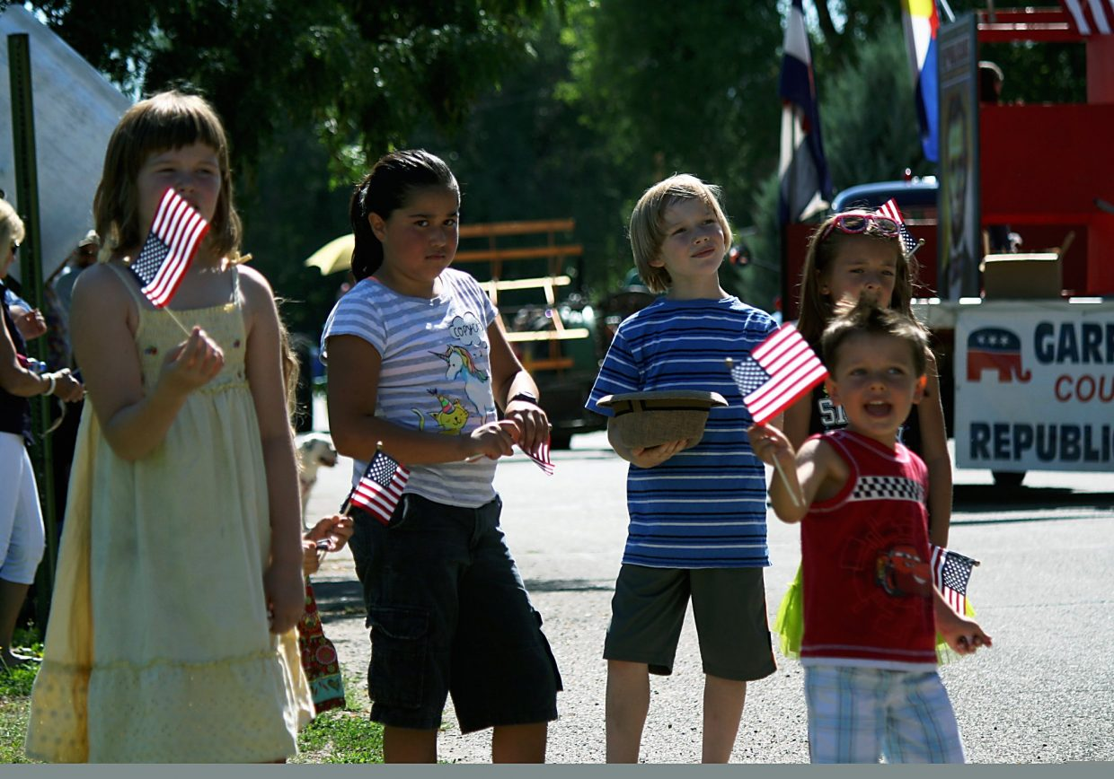 A group of children wave American flags Saturday as floats in the Silt HeyDays parade go down Grand Avenue.