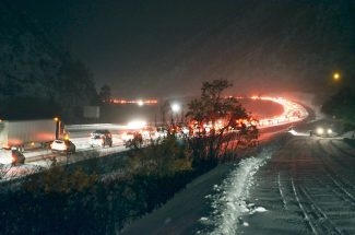 Motorists crawl along westbound Interstate 70 on the outskirts of West Glenwood on Tuesday night. A car accident an estimated three miles west of Glenwood, coupled with snowfall, forced a traffic backup that extended near Exit 116 in Glenwood.