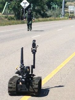 A bomb technician and a robot investigate a suspicious item that led to a closure of Interstate 70 near DeBeque for nearly four hours Tuesday afternoon. The item turned out to be a non-explosive piece of equipment.