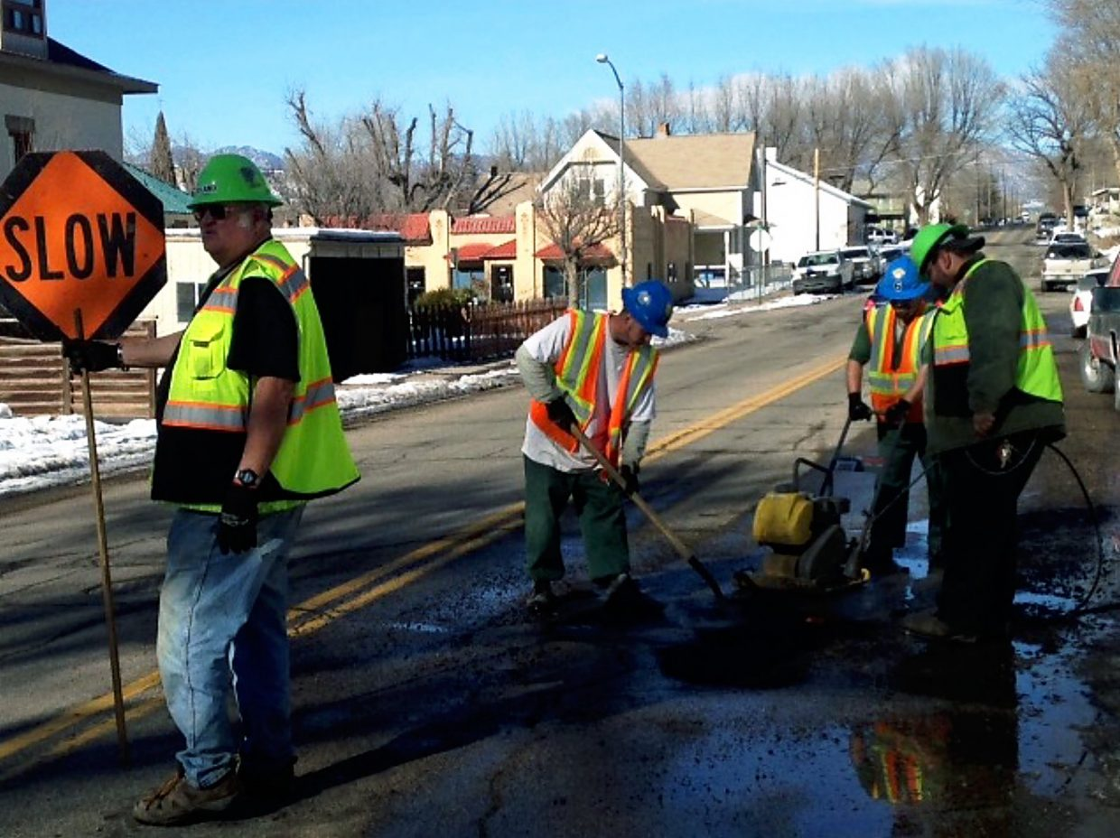 Roland Klocker, left, directs traffic as fellow members of the Rifle Operations and Maintenance department repair a pothole on Whiteriver Avenue.