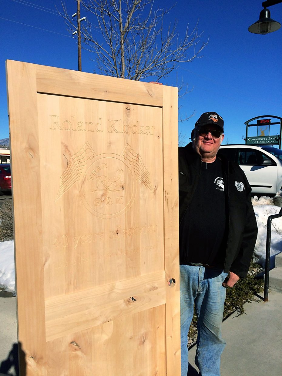 Roland Klocker stands next to a wooden door given to him as a retirement gift on Jan. 28, his last day working for the city after more than 40 years on the job. The door is engraved with the Rifle Operations and Maintenance logo and state that it is the door to his retirement.