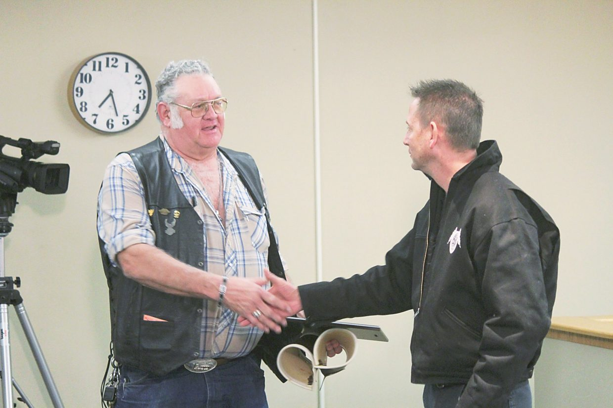 Roland Klocker, left, shakes hands with Rifle Public Works Superintendent Bobby O'Dell at a City Council meeting Feb. 3.