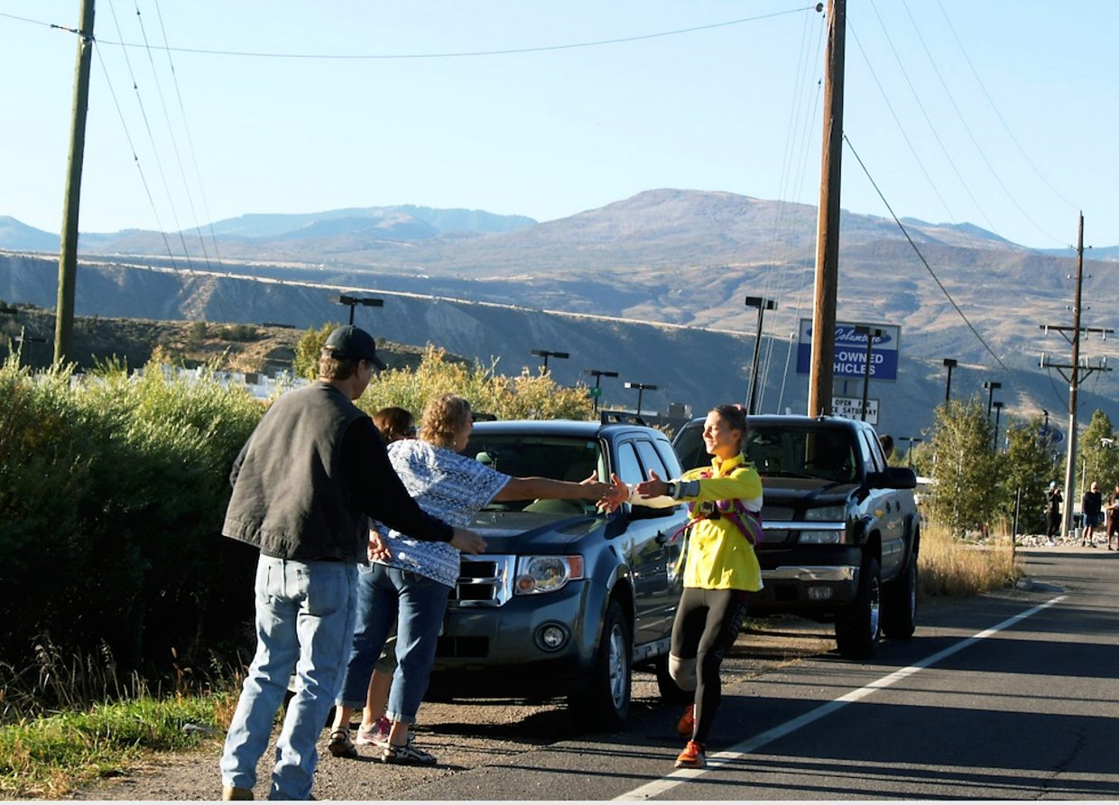Jenny LaBaw stops to hug supporters on Highway 13 in north Rifle Thursday.