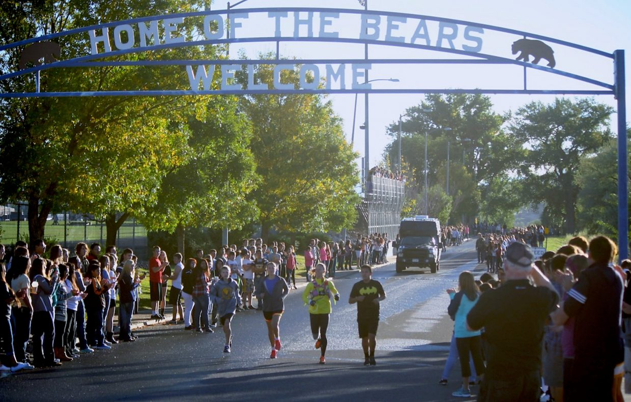 Students and staff line the driveway at Rifle High School Thursday morning as Jenny LaBaw runs toward County Road 244.