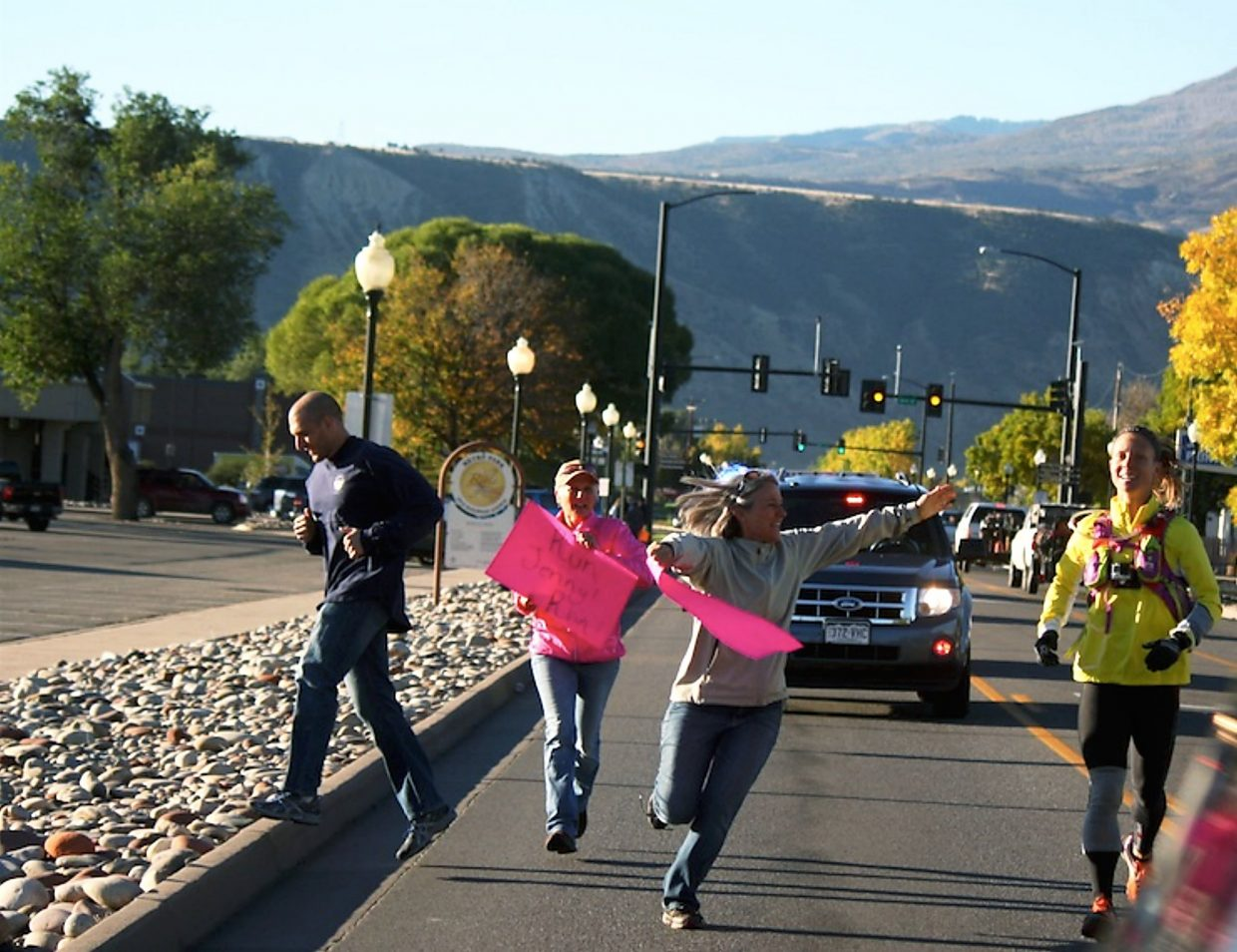 Supporters run alongside Jenny LaBaw on Railroad Avenue in Rifle Thursday.