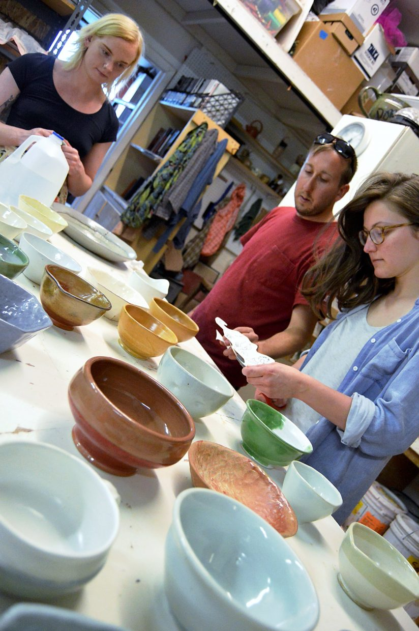 Carbondale Clay Center resident artists Susie Pentelow and Matt Eames and volunteer Katie Bullock apply decals to about 60 bowls for Cajun Clay.
